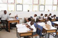 Bambini d'istruzione dell'insegnante dal suo scrittorio ad una scuola elementare Fotografia Stock Libera da Diritti