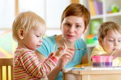 Bambini d'istruzione della donna da dipingere Fotografia Stock Libera da Diritti