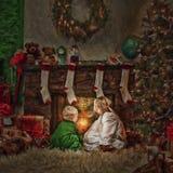 Bambini davanti a fuoco al Natale fotografia stock libera da diritti