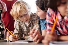 Bambini dedicati intelligenti che discutono le edizioni scientifiche Fotografie Stock