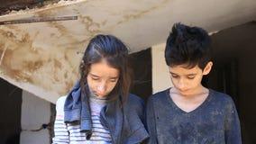 Bambini del rifugiato con un bambino nelle loro armi sui precedenti delle case bombardate Guerra, terremoto, fuoco stock footage