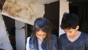 Bambini del rifugiato contro lo sfondo delle case bombardate Guerra, terremoto, fuoco archivi video