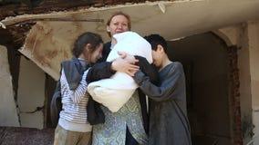 Bambini del rifugiato e la loro madre con un bambino nelle armi sui precedenti delle case bombardate Guerra, terremoto, fuoco stock footage