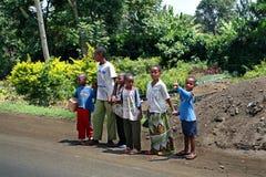 Bambini dell'africano nero che attraversano strada, Tanzania. Fotografia Stock