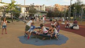 Bambini dell'età differente che giocano sulla rotonda del campo da giuoco, sorridere felice dei bambini stock footage