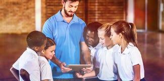 Bambini dell'insegnante e della scuola di sport facendo uso della compressa digitale nel campo da pallacanestro Immagine Stock
