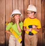 Bambini della costruzione in caschi che tengono un trapano e un livello taglio immagini stock