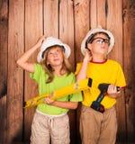 Bambini della costruzione in caschi e con gli strumenti che pensano duro fotografie stock libere da diritti
