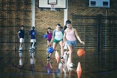 Bambini della High School che praticano calcio facendo uso dei coni per il trapano di gocciolamento immagini stock libere da diritti