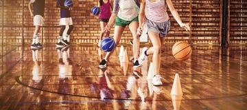 Bambini della High School che praticano calcio facendo uso dei coni per il trapano di gocciolamento immagine stock libera da diritti