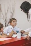 Bambini della ragazza e del ragazzo con l'insegnante nella scuola Fotografie Stock Libere da Diritti