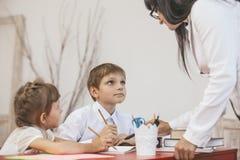Bambini della ragazza e del ragazzo con l'insegnante nella scuola Immagine Stock Libera da Diritti