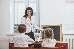 Bambini della ragazza e del ragazzo con l'insegnante nella scuola Fotografia Stock Libera da Diritti