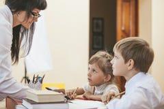 Bambini della ragazza e del ragazzo con l'insegnante nella scuola Fotografie Stock