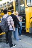 Bambini della scuola che aspettano per salire il bus Immagini Stock Libere da Diritti