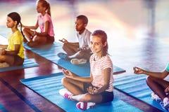 Bambini della scuola che meditano durante la classe di yoga Immagine Stock
