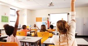 Bambini della scuola che sollevano mano in aula stock footage