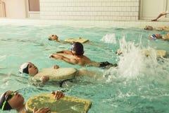 Bambini della scuola elementare all'interno della lezione di nuoto di abilità fotografia stock libera da diritti