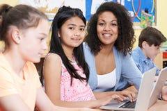 Bambini della scuola elementare di Helping Group Of dell'insegnante in computer immagini stock libere da diritti