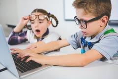 Bambini della scuola facendo uso di un computer portatile in aula Immagine Stock Libera da Diritti