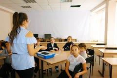 Bambini della scuola nella classe con la donna dell'insegnante Fotografia Stock Libera da Diritti