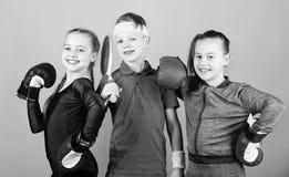 Bambini delle ragazze con l'attrezzatura di sport di pugilato ed il tennis del ragazzo Modi aiutare i bambini a trovare sport che immagini stock