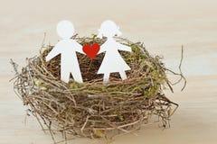Bambini di carta con un cuore in nido - concetto di protezione del bambino immagine stock