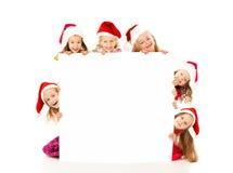 Bambini di Natale con l'insegna bianca Fotografia Stock
