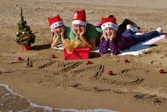 Bambini di natale felice sulla spiaggia Fotografia Stock