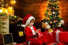 Bambini di Natale Il bambino felice sta indossando i vestiti di Santa, giocanti con il contenitore di regalo di Natale Fondo del  immagine stock