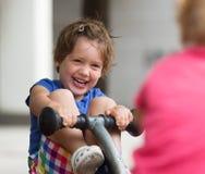 Bambini divertendosi al campo da giuoco Fotografia Stock Libera da Diritti