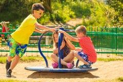 Bambini divertendosi sul campo da giuoco Fotografie Stock Libere da Diritti