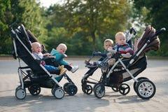 Bambini divertenti che si siedono in passeggiatori in parco Immagini Stock