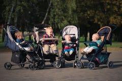 Bambini divertenti che si siedono in passeggiatori in parco Fotografie Stock