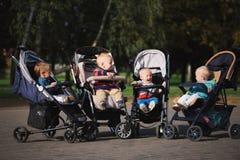 Bambini divertenti che si siedono in passeggiatori in parco Fotografia Stock