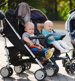 Bambini divertenti che si siedono in passeggiatori in parco Immagine Stock Libera da Diritti
