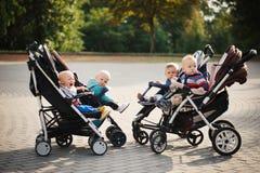 Bambini divertenti che si siedono in passeggiatori in parco Fotografia Stock Libera da Diritti