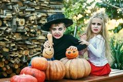 Bambini divertenti in costumi con le zucche immagini stock