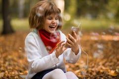 Bambini e concetto di tecnologia - ragazza con lo smartphone che ha video chiamata immagini stock