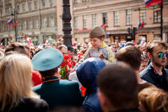 Bambini e fiore rosso sopra massa della gente Fotografia Stock