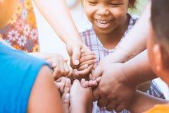 Bambini e genitore che si tengono per mano insieme e che giocano fotografia stock libera da diritti