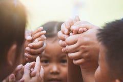 Bambini e genitore che si tengono per mano insieme e che giocano immagini stock
