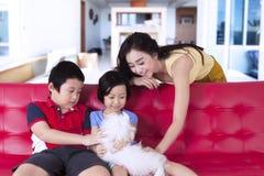 Bambini e gioco della madre con il cane sveglio Immagine Stock Libera da Diritti