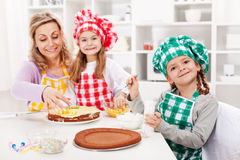 Bambini e la loro madre che fanno una torta Fotografie Stock Libere da Diritti