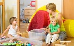 Bambini e madre che raccolgono i giocattoli fotografie stock