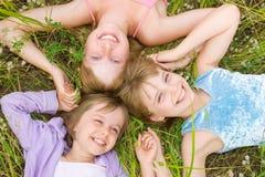 Bambini e ragazze graziosi dell'adolescente su erba verde Immagine Stock