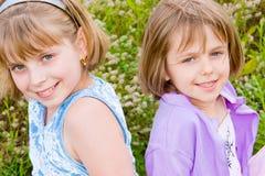 Bambini e ragazze graziosi dell'adolescente su erba verde Fotografie Stock