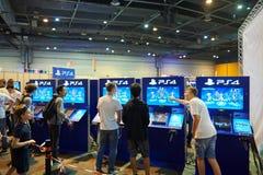 Bambini ed adulti che giocano le consoli del gioco di PS 4 Fotografia Stock Libera da Diritti