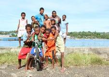 Bambini ed anni dell'adolescenza che posano sulla banca del mare in Manokwari Immagini Stock