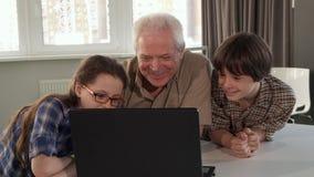 Bambini ed il loro nonno che guardano qualcosa sul computer portatile immagini stock